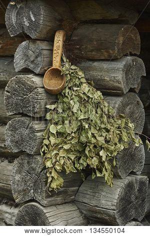 bunch of green birch twigs and scoop on lumber wall corner close up