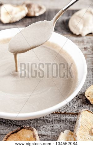 Creamy vegan mushroom soup with champignon and shiitake in white bowl. Soup drains from spoon into bowl. Wood background. Dry shiitake on front.