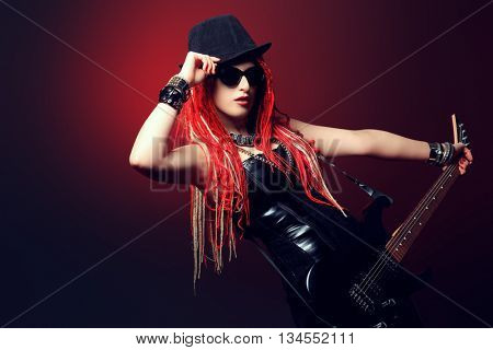 Modern girl rock musician is playing the electric guitar.