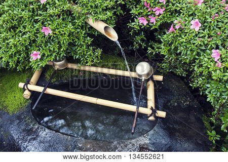 traditional Japanese water basin Tsukubai fragment with bamboo pipe water source