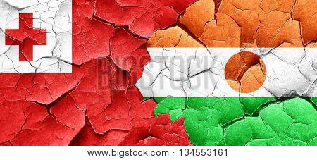 Tonga flag with Niger flag on a grunge cracked wall