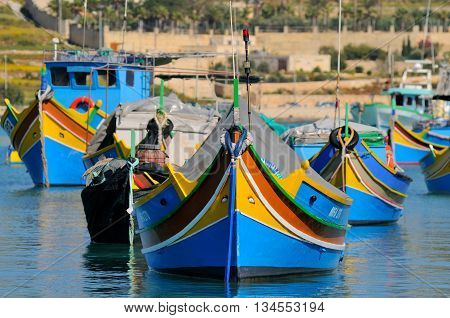 MARSAXLOKK MALTA - APR 18 :The iconic Malta fishing boats in the Marsaxlokk village in Malta April 18 2011. They are usually painted in bright colours while the bow has a pair of eyes