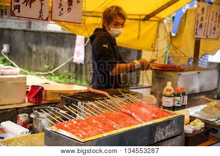 KYOTO JAPAN - NOVEMBER 19 2015 : A man grills red stick crab meat Traditional Japanese street food in Kyoto Japan