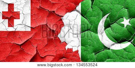 Tonga flag with Pakistan flag on a grunge cracked wall