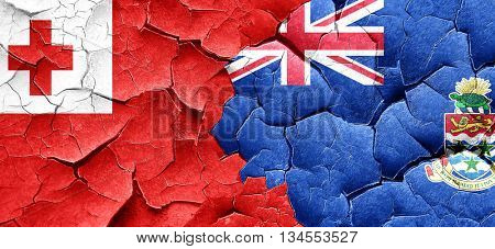 Tonga flag with Cayman islands flag on a grunge cracked wall