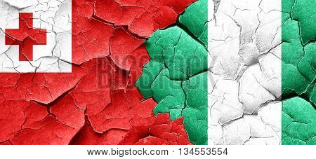 Tonga flag with Nigeria flag on a grunge cracked wall
