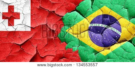 Tonga flag with Brazil flag on a grunge cracked wall
