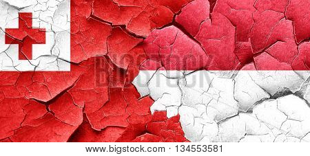 Tonga flag with Indonesia flag on a grunge cracked wall