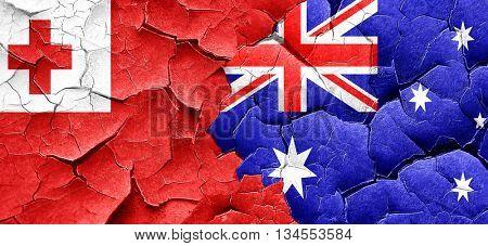 Tonga flag with Australia flag on a grunge cracked wall