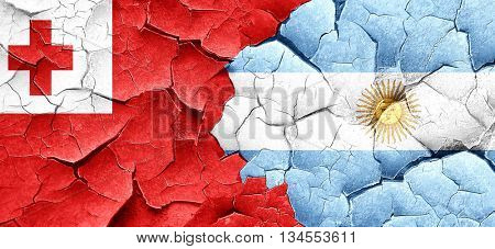 Tonga flag with Argentine flag on a grunge cracked wall