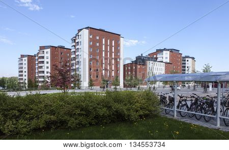 UMEA, SWEDEN ON JUNE 02. View of buildings, apartments from opposite side a street on June 02, 2016 in Umea, Sweden. Park and shelter for bicycles this side. Editorial use.