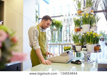 people, sale, retail, business and floristry concept - happy smiling florist man with cashbox standing at flower shop counter
