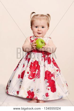 Beautiful baby girl with green apple on a light background. Retro toning