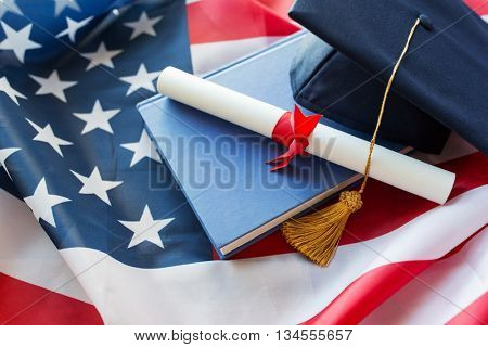 education, graduation, patriotism and nationalism concept - close up of bachelor hat and diploma on american flag