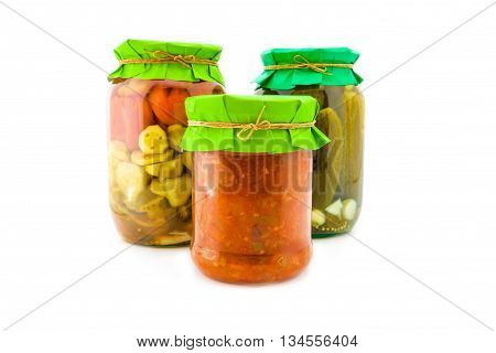 Homemade pickled green and red tomatoes with cucumbers, squash caviar, carrots and onions in glass jar with paper wrapper. Jars with preservation isolated on white background