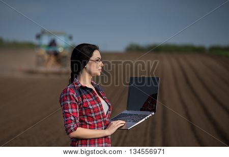 Farmer Girl With Laptop In Field With Tractor