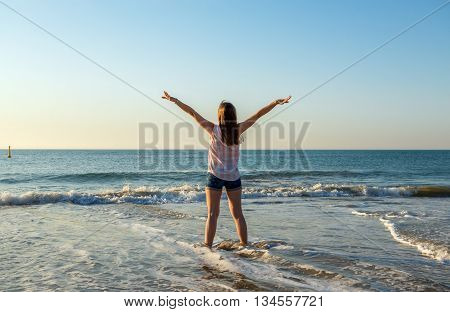 Happy young woman enjoys summer and sea in the evening light.Vacationtravel and freedom concept