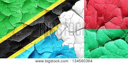 Tanzanian flag with Madagascar flag on a grunge cracked wall
