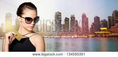 shopping, finances, fashion, people and luxury concept - beautiful young woman in elegant black sunglasses with credit card over dubai night city lights street background