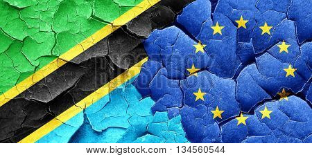 Tanzanian flag with european union flag on a grunge cracked wall