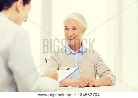 medicine, age, health care and people concept - doctor with clipboard writing prescription for senior woman at hospital