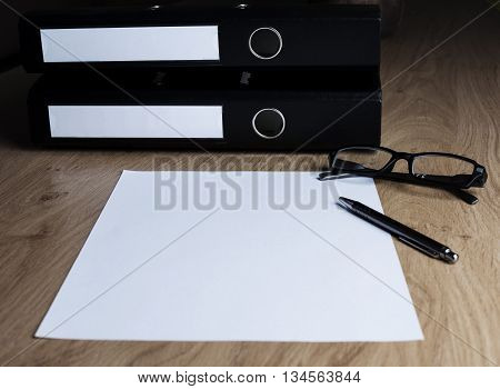 Table with folders, empty white sheet, glasses and pen