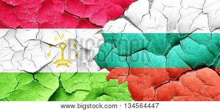 Tajikistan flag with Bulgaria flag on a grunge cracked wall