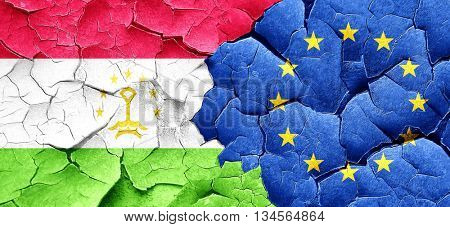 Tajikistan flag with european union flag on a grunge cracked wal