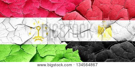 Tajikistan flag with egypt flag on a grunge cracked wall