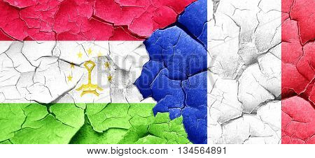 Tajikistan flag with France flag on a grunge cracked wall