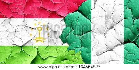 Tajikistan flag with Nigeria flag on a grunge cracked wall