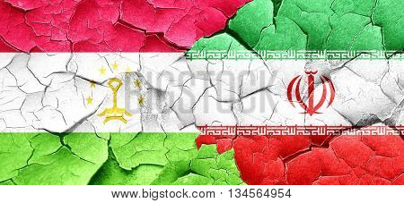 Tajikistan flag with Iran flag on a grunge cracked wall