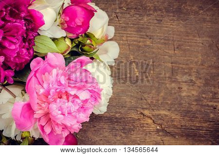 Peony background. Fuchsia, pink and white peonies on wooden table with place for text. Spring flower peony. Happy Mothers Day. Mother's Day greetings card. Mothers Day gift. Copy space.