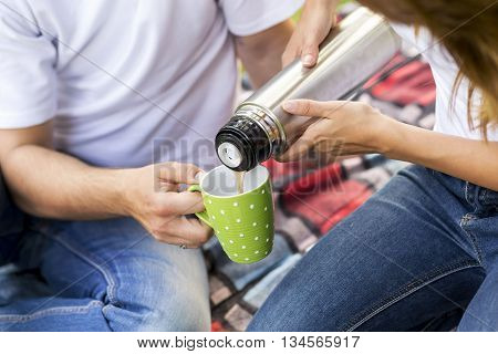 Young couple on a picnic in a park. Girl pouring hot coffee from a thermos bottle