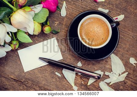 A cup of coffee and flowers Peonies on a wooden table with an empty card for text and pen. Breakfast on Mothers day, Valentines Day or Womens day. Writing greetings card. Copy space. Top view.