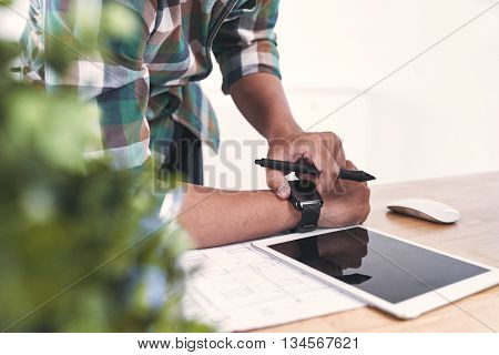 Young designer looking at his watch while working over blueprint