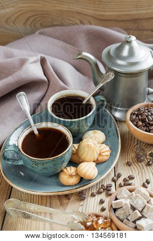 Two blue cups of black coffee cookies and coffee pot surrounded by linen cloth sugar pieces and coffee beans on old wooden table; vertical image