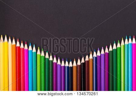 Color pencils pile arrangement on black background