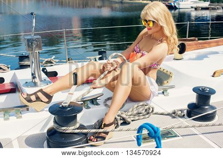 Young beautiful woman in color two-piece swimsuit discloses sail on yacht at sunny day