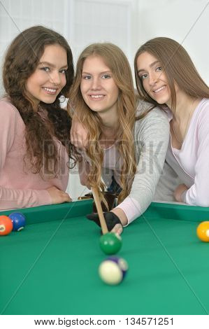 Portrait of a young girls with cue playing billiard