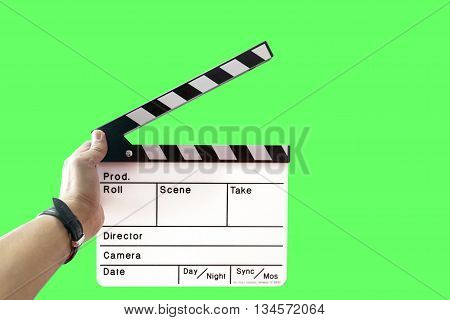 Men's hand holding camera slate  for the filming isolated on green background.
