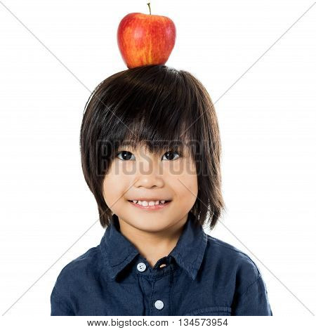 Close up portrait of funny asian boy with red apple on head.Isolated on white background.