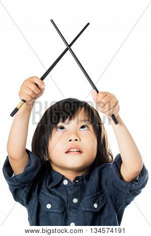Close up portrait of little Asian boy playing with chopsticks looking up.Isolated on white background.