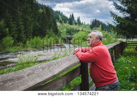 Full length portrait of a standing senior man outdoors. Serious senior man in the peaceful quiet place thinking about something and resting. Beautiful mountains landscape with river.