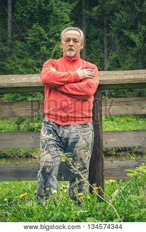 Full length portrait of a handsome senior man in bright sweater near the wooden fence in the forest. Looking at the camera. Serious senior man with gray hair and beard on excursion. Vertical image.