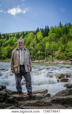 Full length portrait of a handsome senior man in the beautiful place. Looking at the camera. Serious senior man with gray hair and beard near the waterfall. Vertical image.