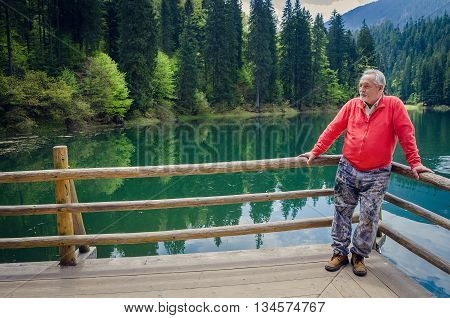 Full length portrait of a handsome senior man in bright sweater near the beautiful forest lake. Looking far away. Serious senior man with gray hair and beard on excursion. Horizontal image.