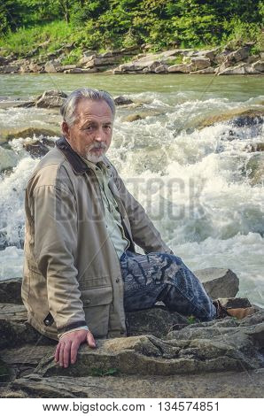 Senior man is sitting and thinking near the waterfall in the beautiful place. Looking at the camera. Serious senior man with gray hair and beard. Vertical image.