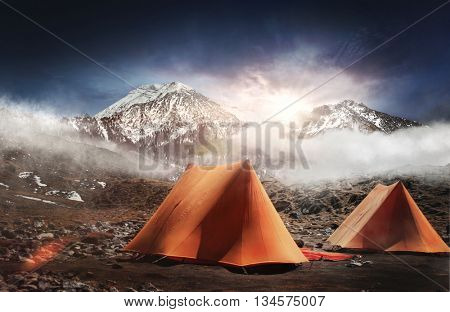 Two tents pitched below snow capped mountains at sunrise with a bright sunburst over the tops of the peaks and early morning mist clinging to the landscape