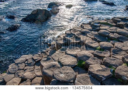 Giants Causeway. Unique geological hexagonal formations of volcanic basalt rocks on the coast in Northern Ireland, UK, in sunset light